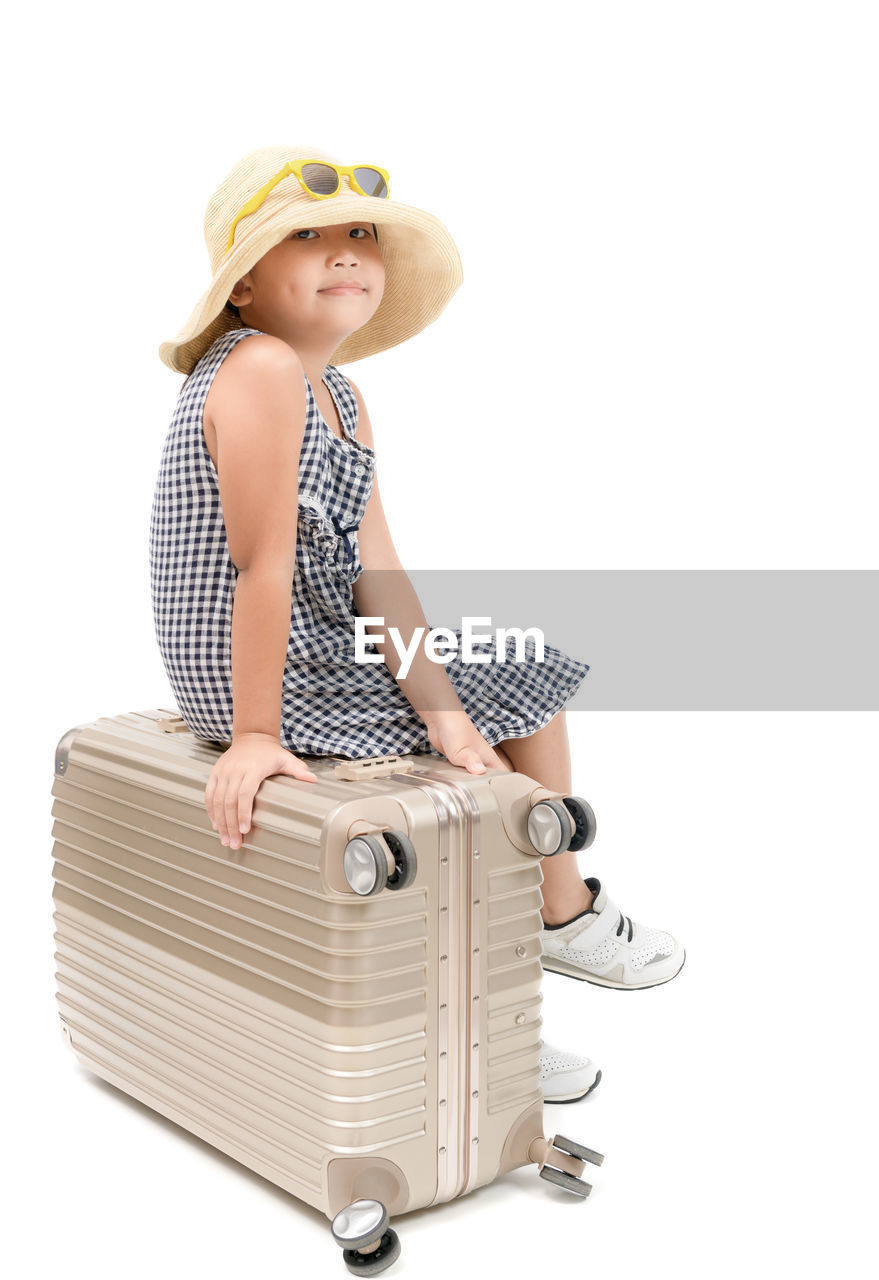 Portrait of girl sitting on suitcase against white background