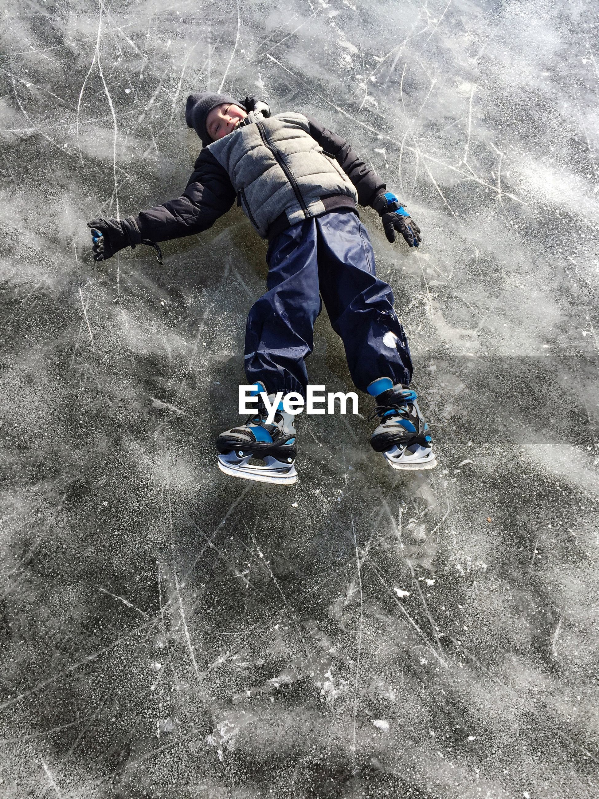 Full length of boy lying on ice rink