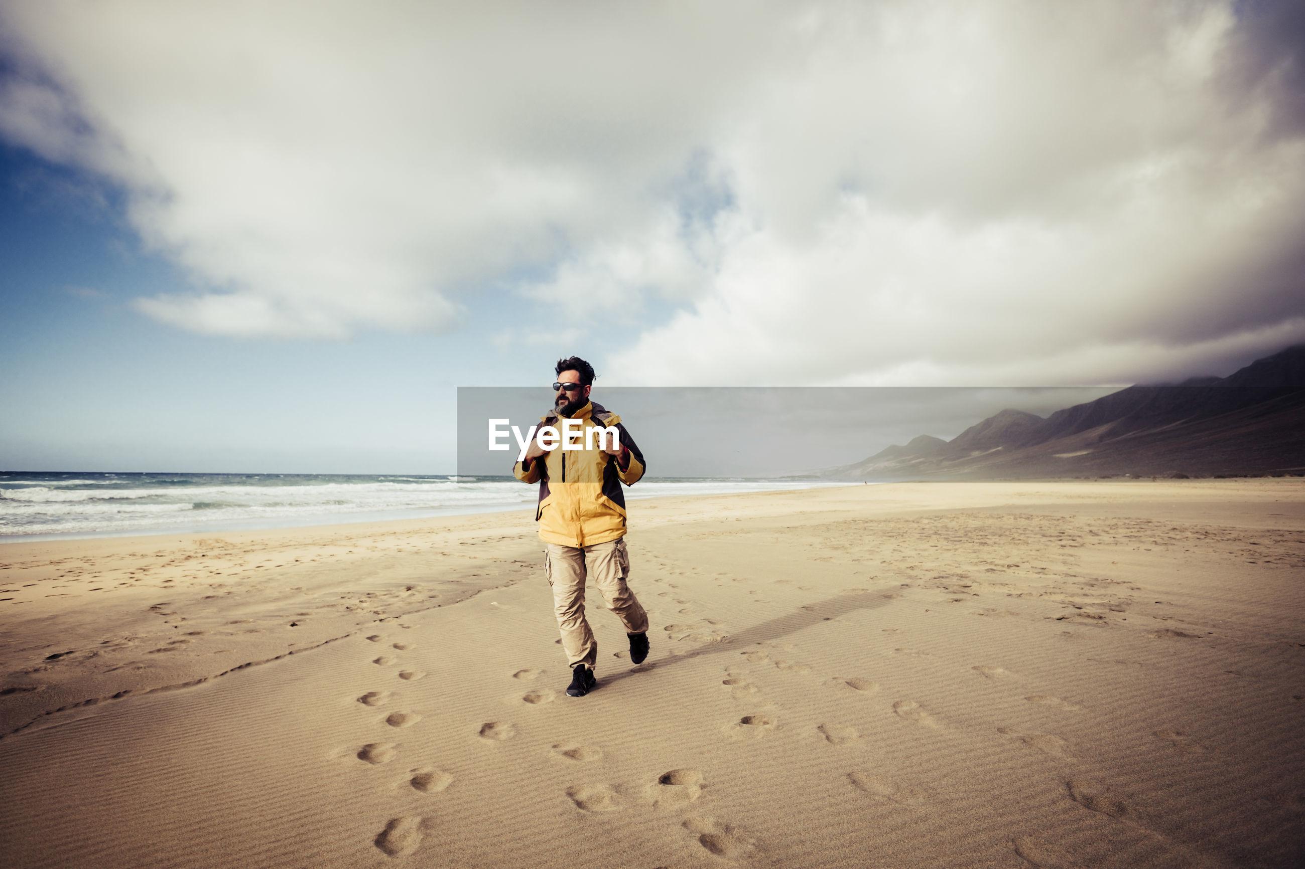 Full length of man walking at beach against sky