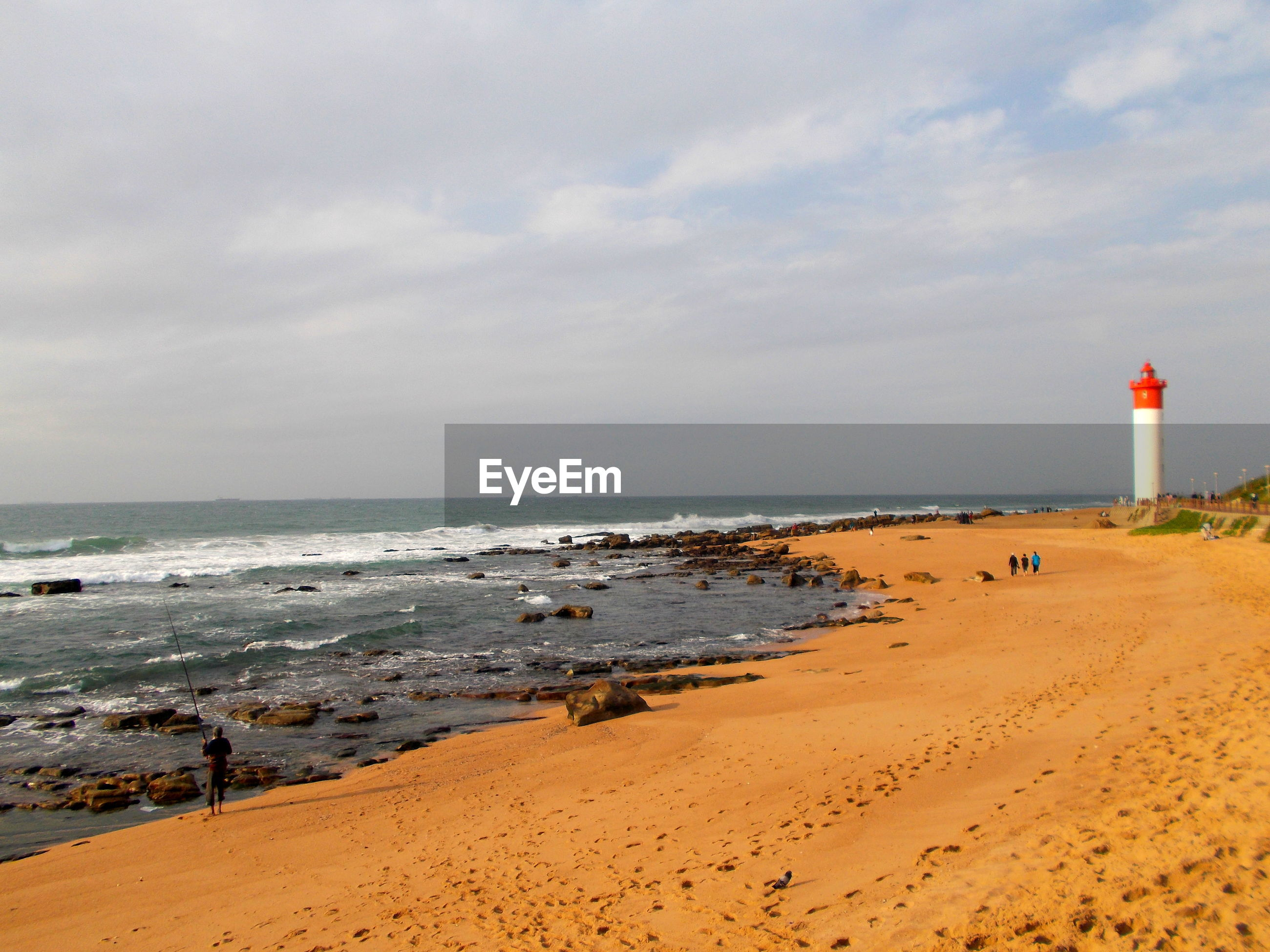Distance shot of lighthouse on calm beach