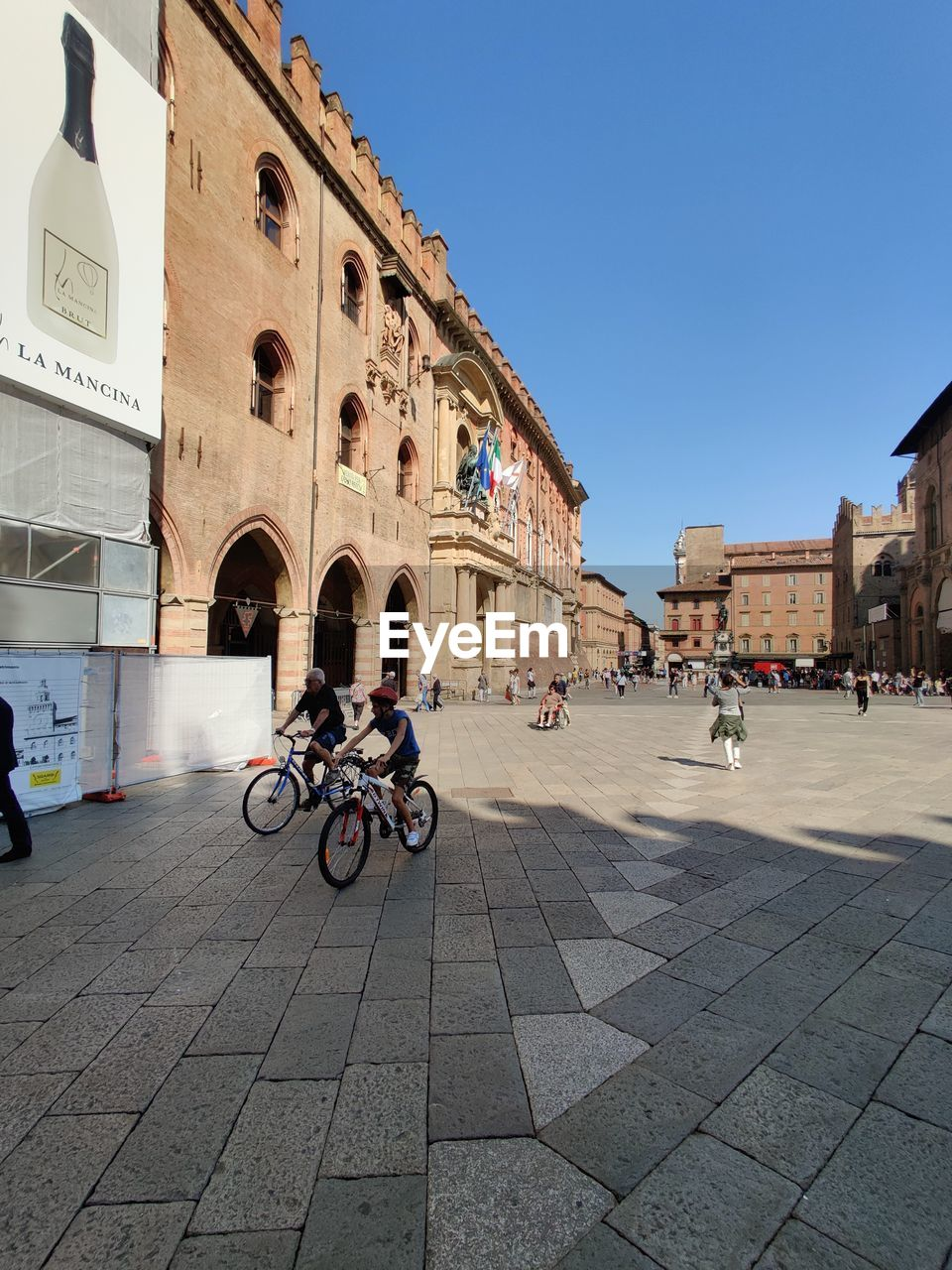 built structure, architecture, building exterior, city, real people, sky, group of people, building, street, women, lifestyles, men, transportation, day, land vehicle, arch, mode of transportation, clear sky, bicycle, incidental people, outdoors
