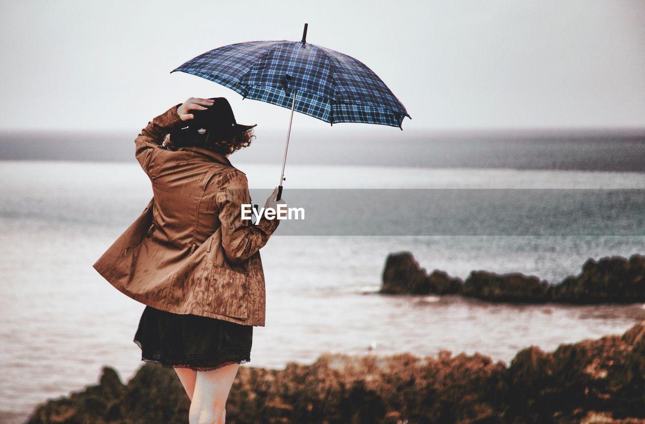 Woman With Umbrella Overlooking Calm Sea