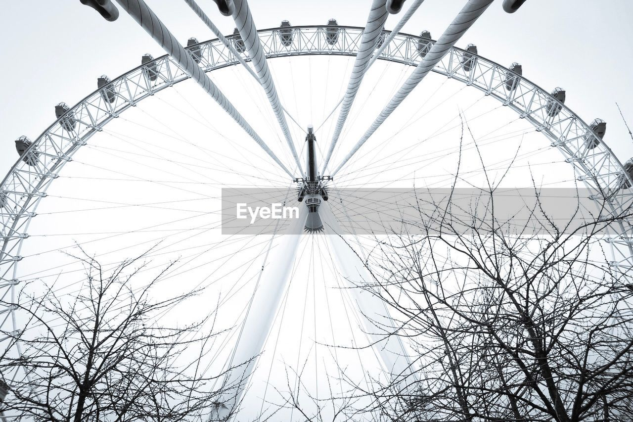 amusement park, low angle view, ferris wheel, arts culture and entertainment, bare tree, big wheel, amusement park ride, no people, sky, day, architecture, built structure, outdoors, clear sky