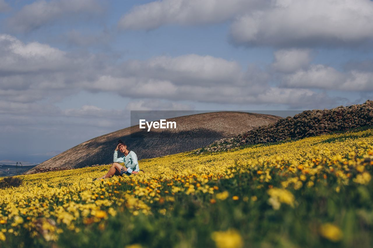 Scenic view of yellow flower on field against sky