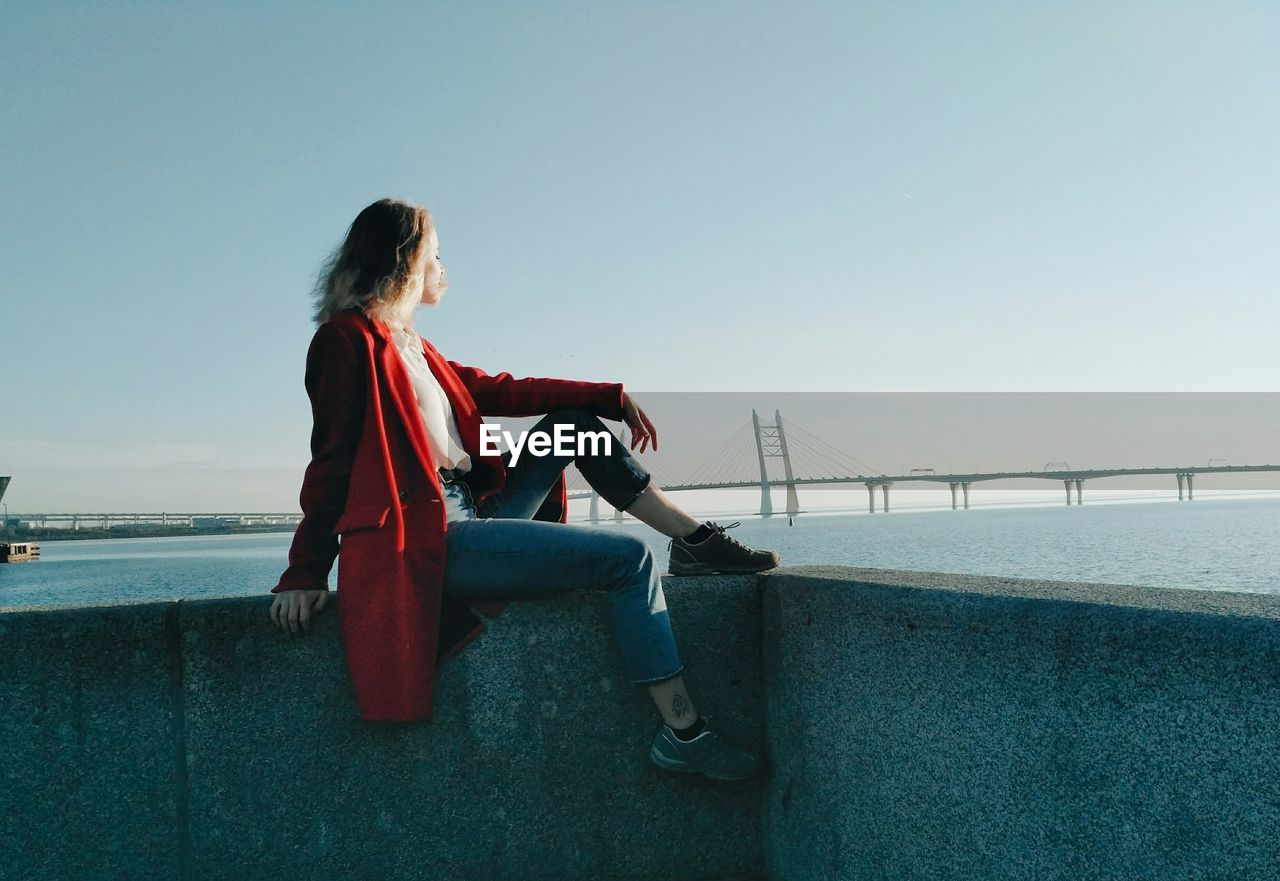 Side View Of Woman Sitting On Retaining Wall By Sea Against Clear Sky