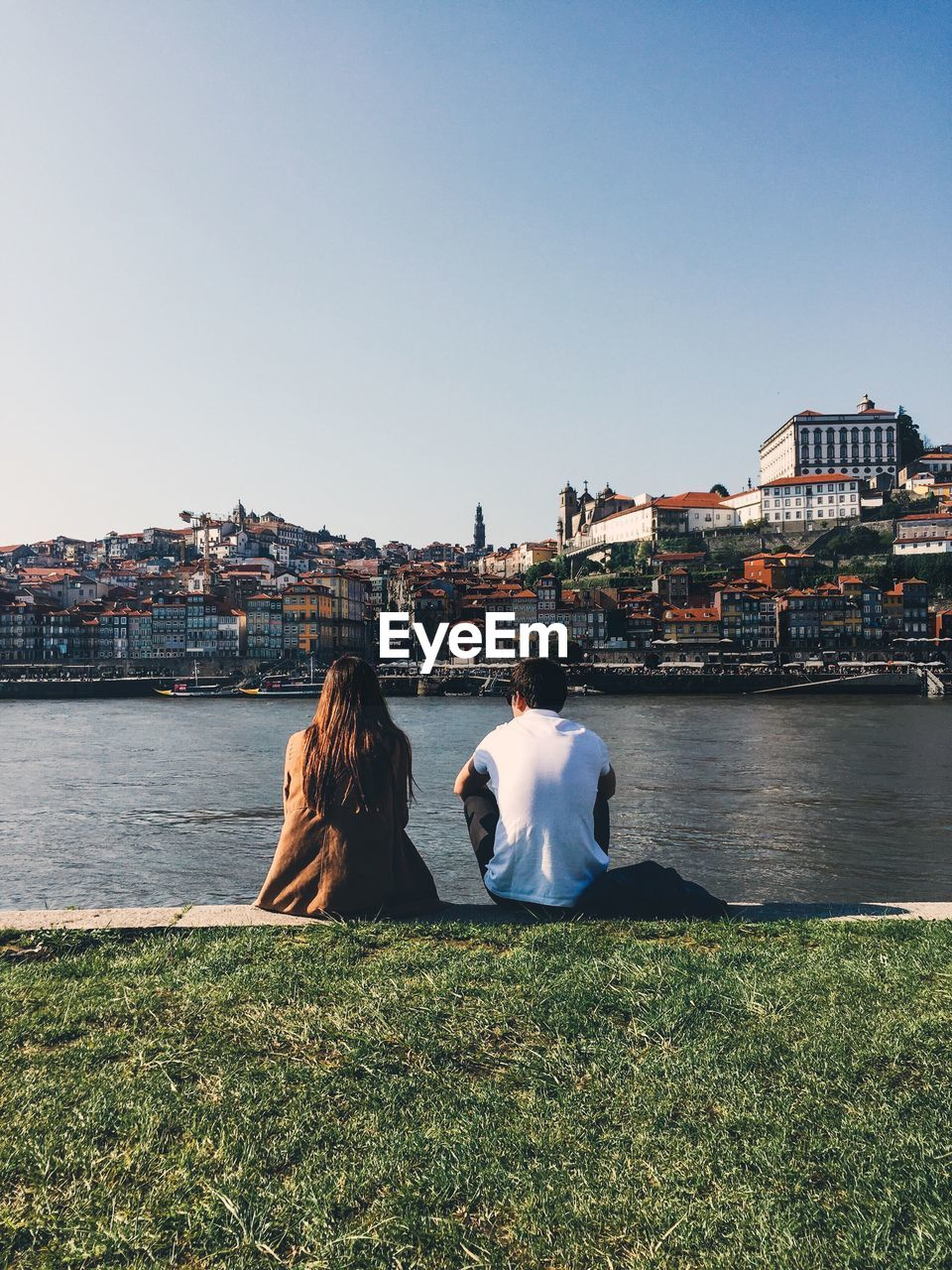 Rear View Of Friends Sitting By River Against Cityscape