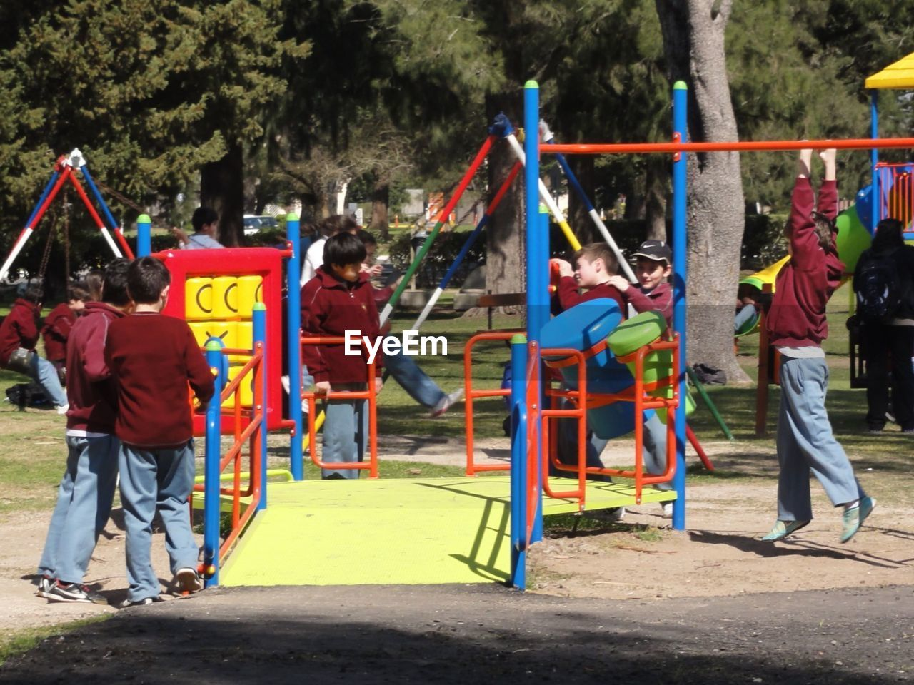 real people, casual clothing, playground, lifestyles, day, flag, leisure activity, full length, outdoors, park - man made space, men, tree, hanging, childhood, multi colored, people
