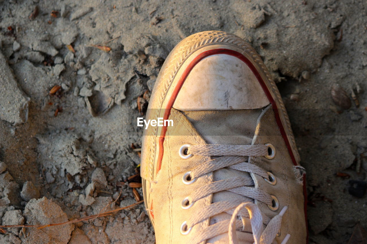 shoe, close-up, day, human body part, dirt, high angle view, nature, shoelace, directly above, outdoors, dirty, solid, land, body part, rock, rock - object, low section, people, personal perspective, human foot, leather