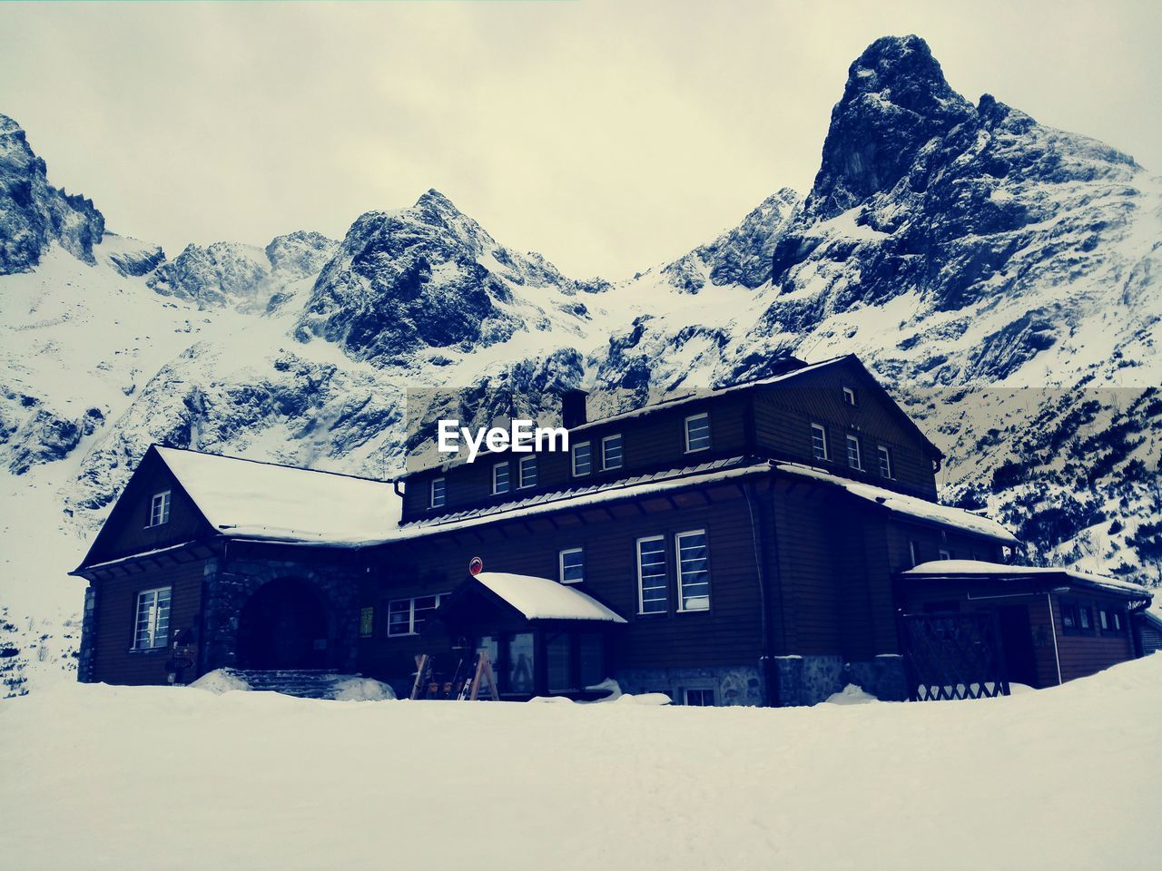 SNOW COVERED HOUSES AGAINST MOUNTAIN RANGE