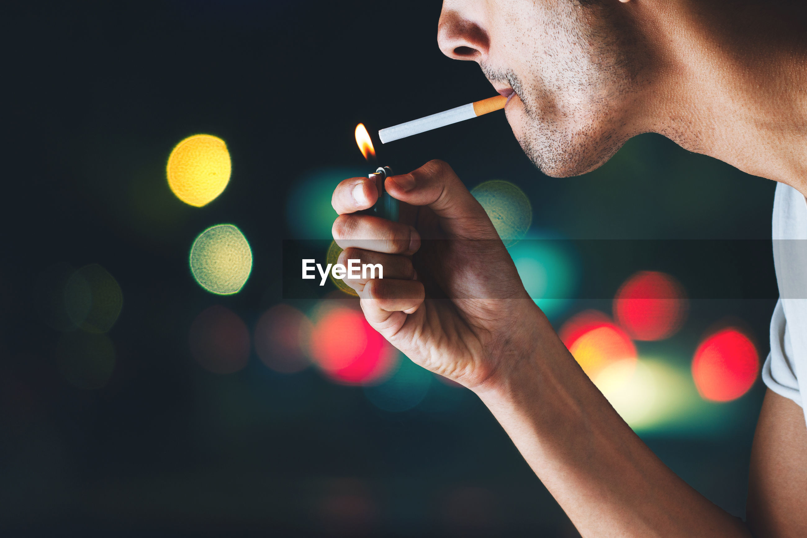 Midsection of man smoking cigarette at night