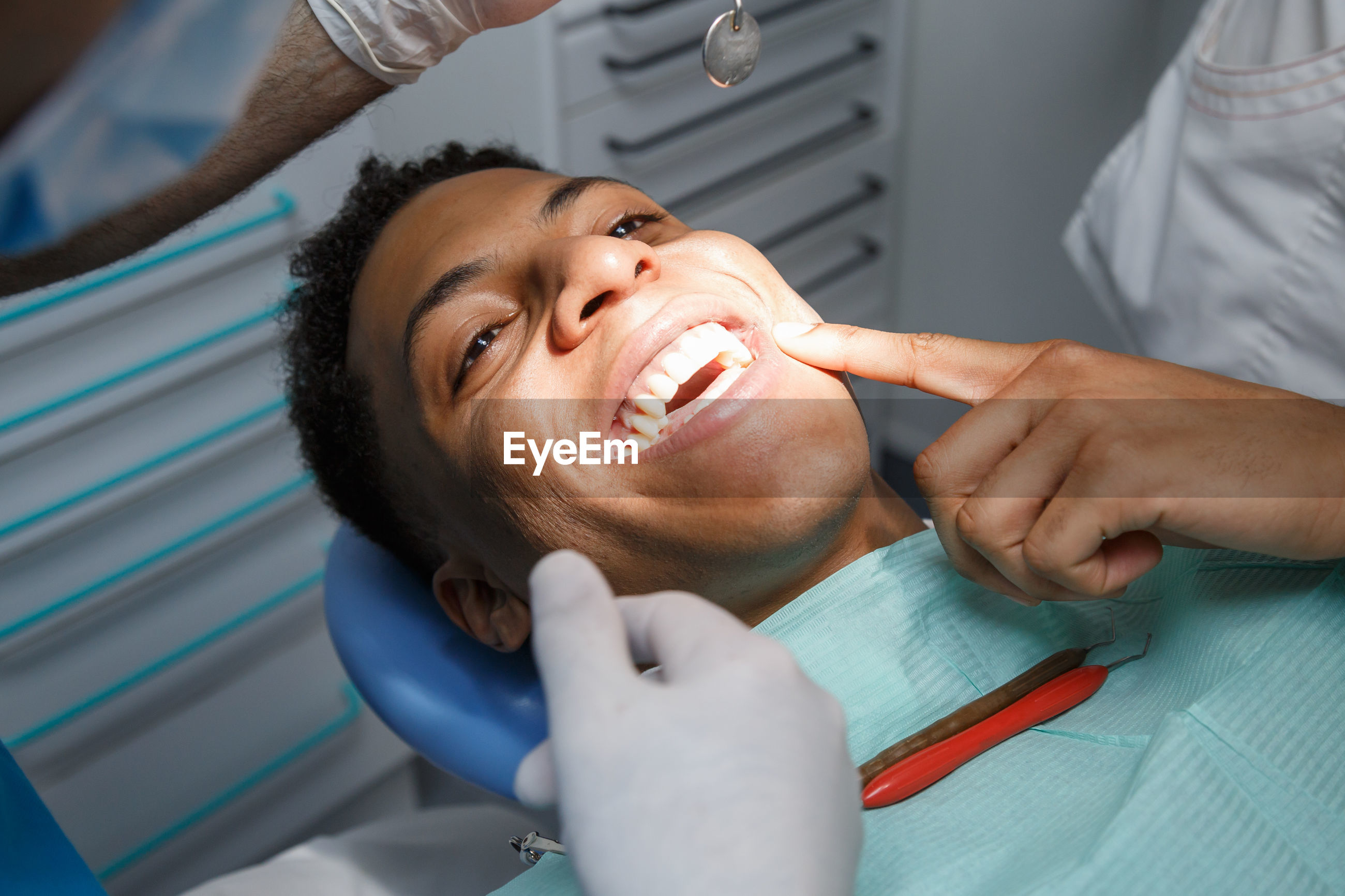 Midsection of dentists examining patient tooth