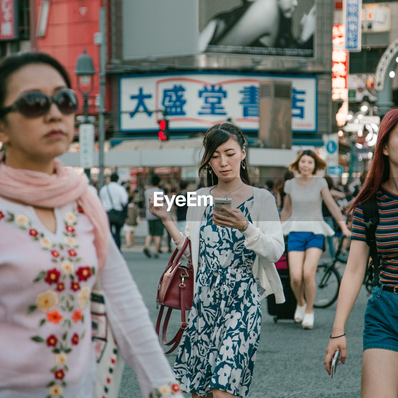 sunglasses, incidental people, real people, casual clothing, outdoors, store, street, day, fashion, young women, city, retail, building exterior, standing, lifestyles, women, young adult, smiling, one person, adult, people