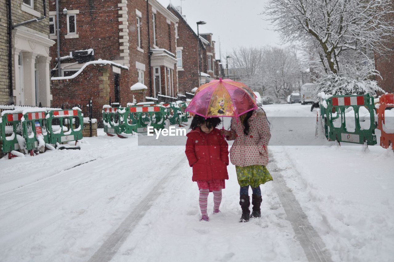 warm clothing, winter, two people, cold temperature, building exterior, built structure, architecture, snow, full length, girls, real people, togetherness, outdoors, childhood, day, tree, happiness, bare tree, lifestyles, snowing, people, adult