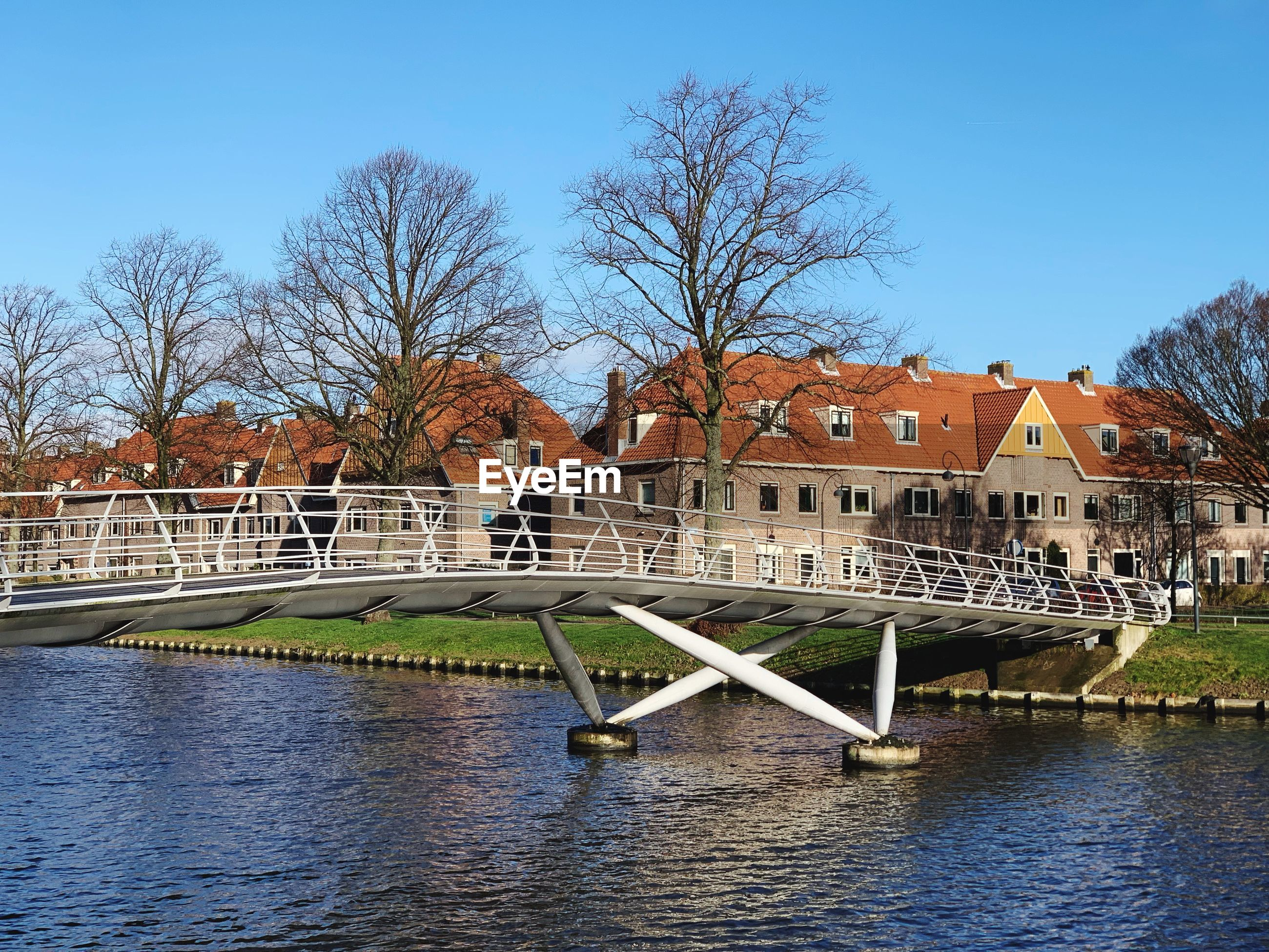 BRIDGE OVER RIVER AND HOUSES AGAINST SKY