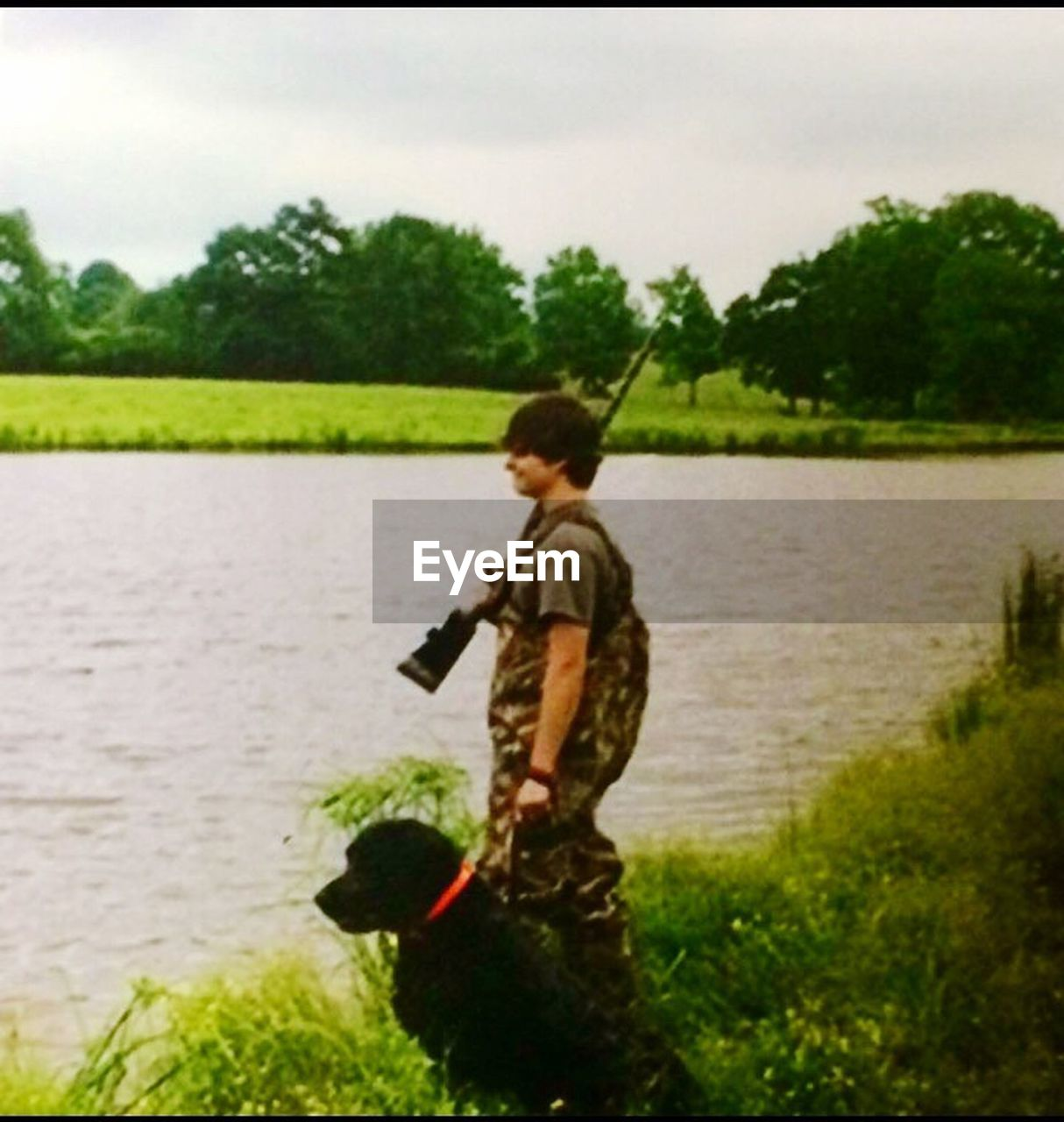 tree, water, one person, standing, childhood, lake, real people, leisure activity, outdoors, day, boys, grass, side view, nature, one animal, sky, full length, one boy only, people
