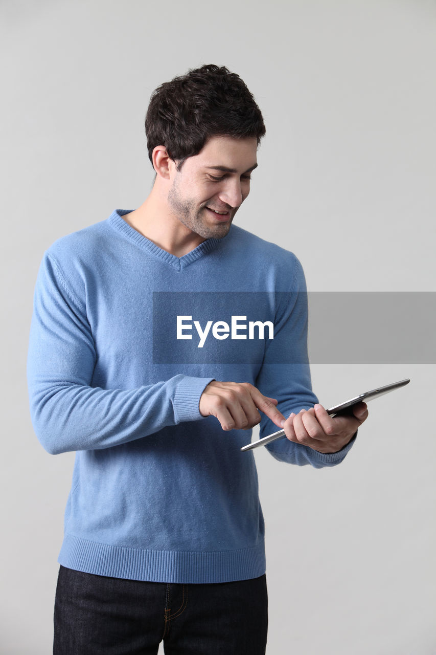 holding, one person, standing, indoors, wireless technology, studio shot, technology, young adult, young men, communication, casual clothing, front view, three quarter length, mobile phone, connection, gray, smiling, men
