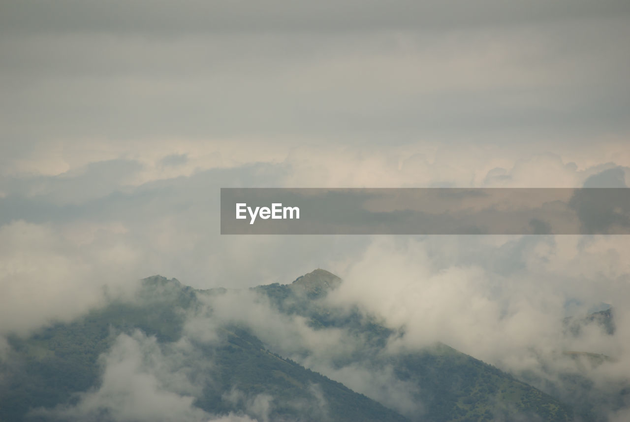 cloud - sky, beauty in nature, sky, scenics - nature, mountain, tranquil scene, tranquility, no people, nature, non-urban scene, day, idyllic, fog, outdoors, mountain range, cloudscape, environment, remote, low angle view, mountain peak, hazy