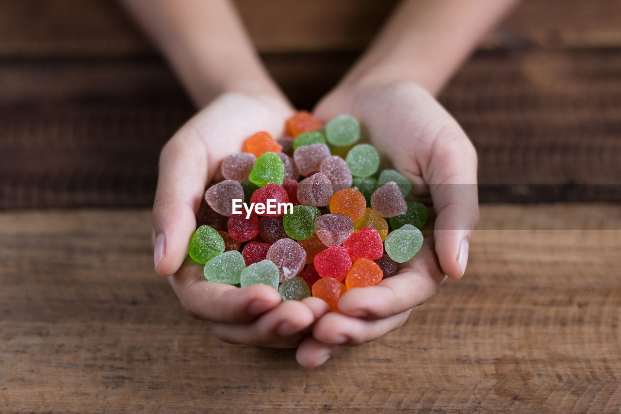 Cropped Hands Of Woman Holding Colorful Candies On Table