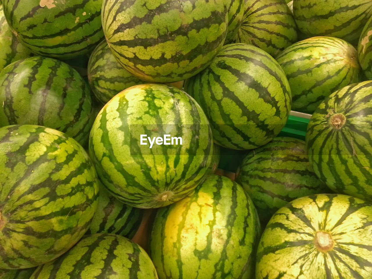 food and drink, food, healthy eating, freshness, wellbeing, green color, fruit, backgrounds, no people, large group of objects, market, full frame, for sale, watermelon, abundance, retail, high angle view, close-up, day, market stall, ripe, outdoors, melon