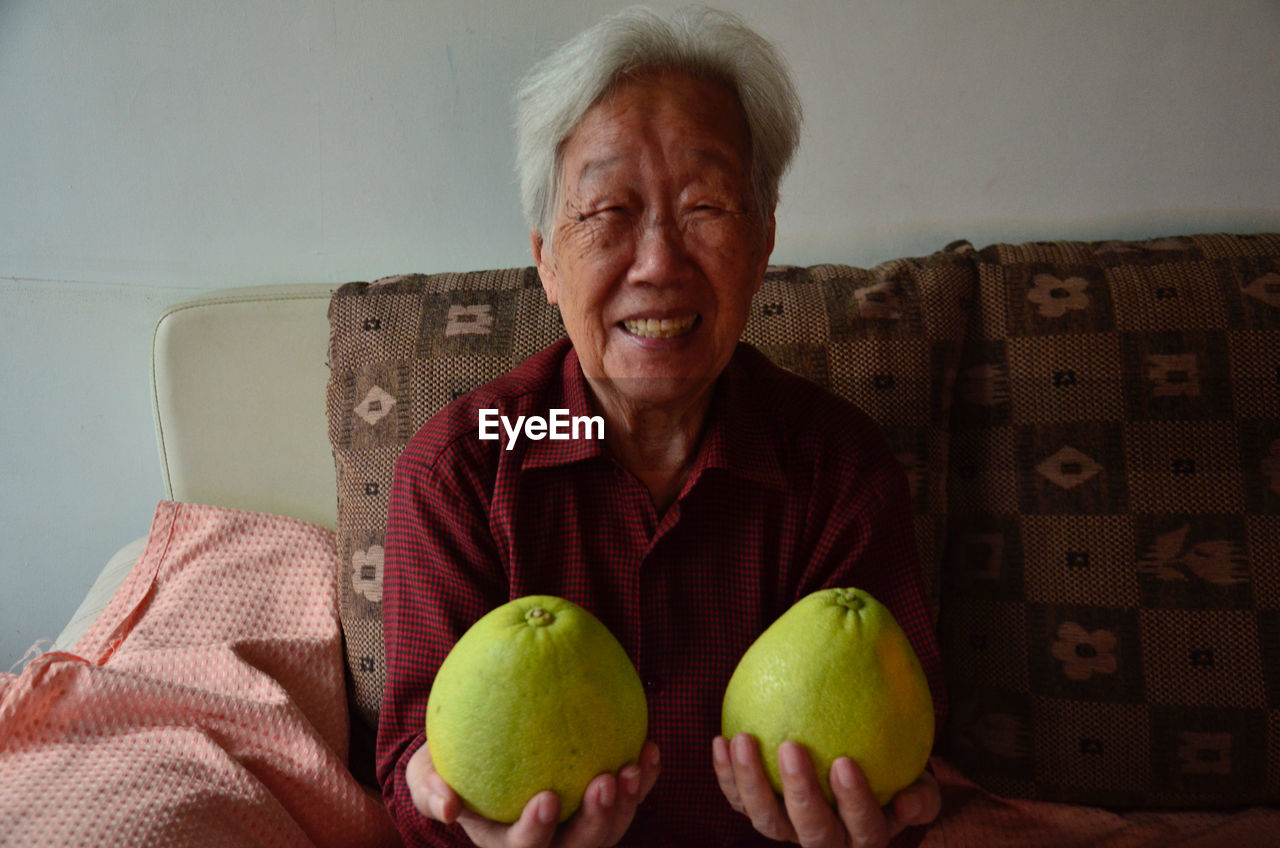 Front View Of Senior Woman Holding Pomelos
