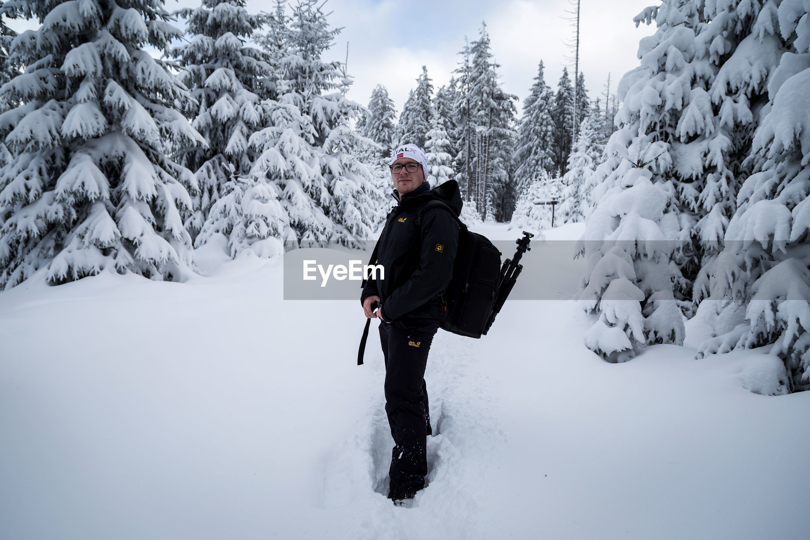 MAN AND WOMAN WALKING ON SNOW COVERED MOUNTAIN