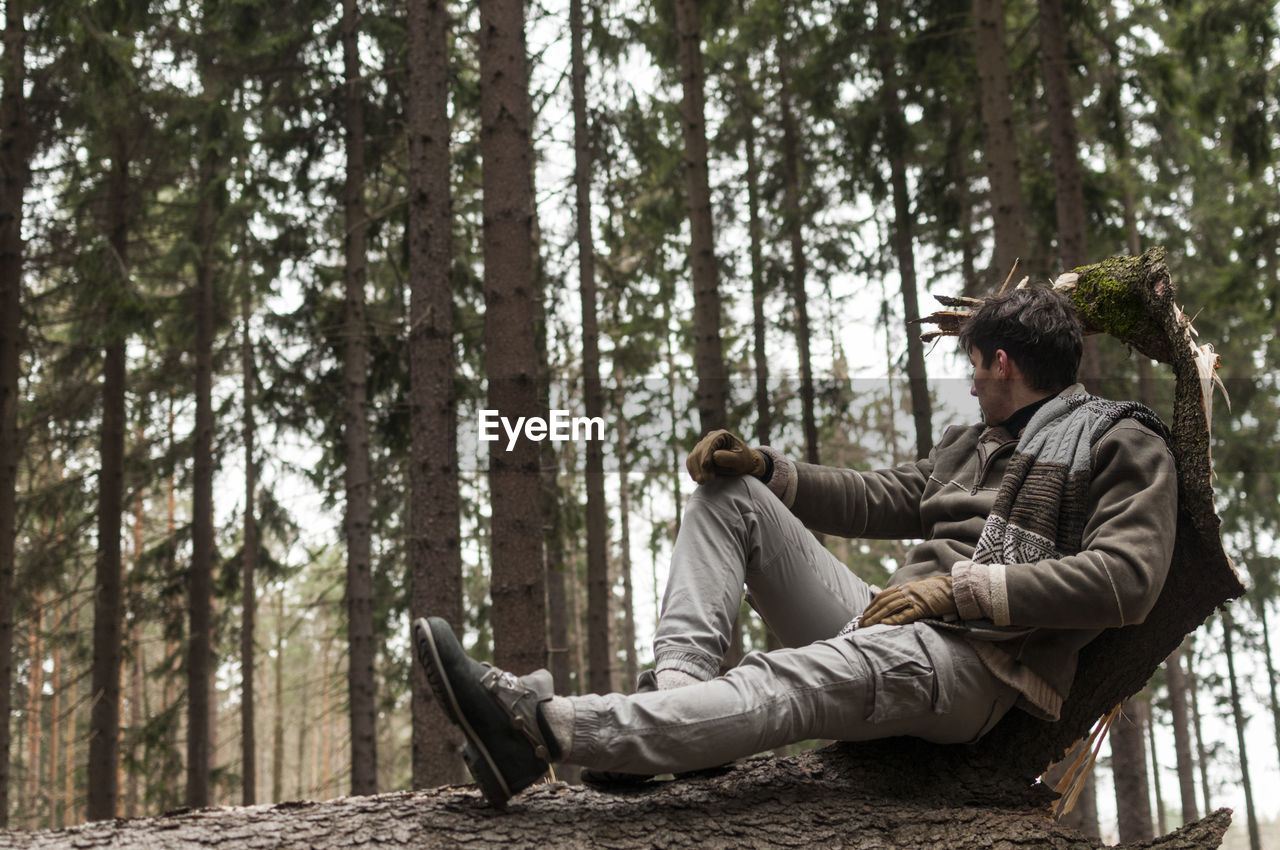 Young Man Sitting On Log In Forest