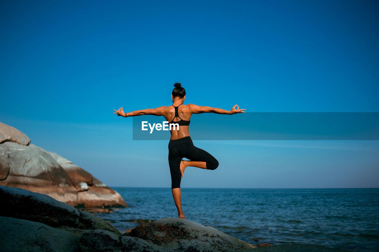 Full Length Of Woman Doing Yoga On Rock Against Sea
