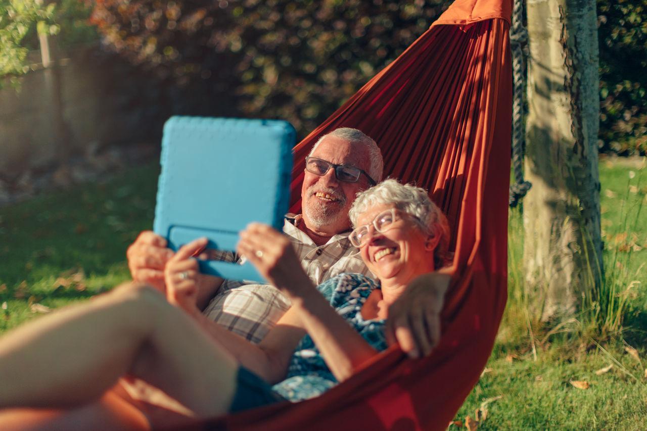Smiling senior couple lying on hammock outdoors in backyard using tablet