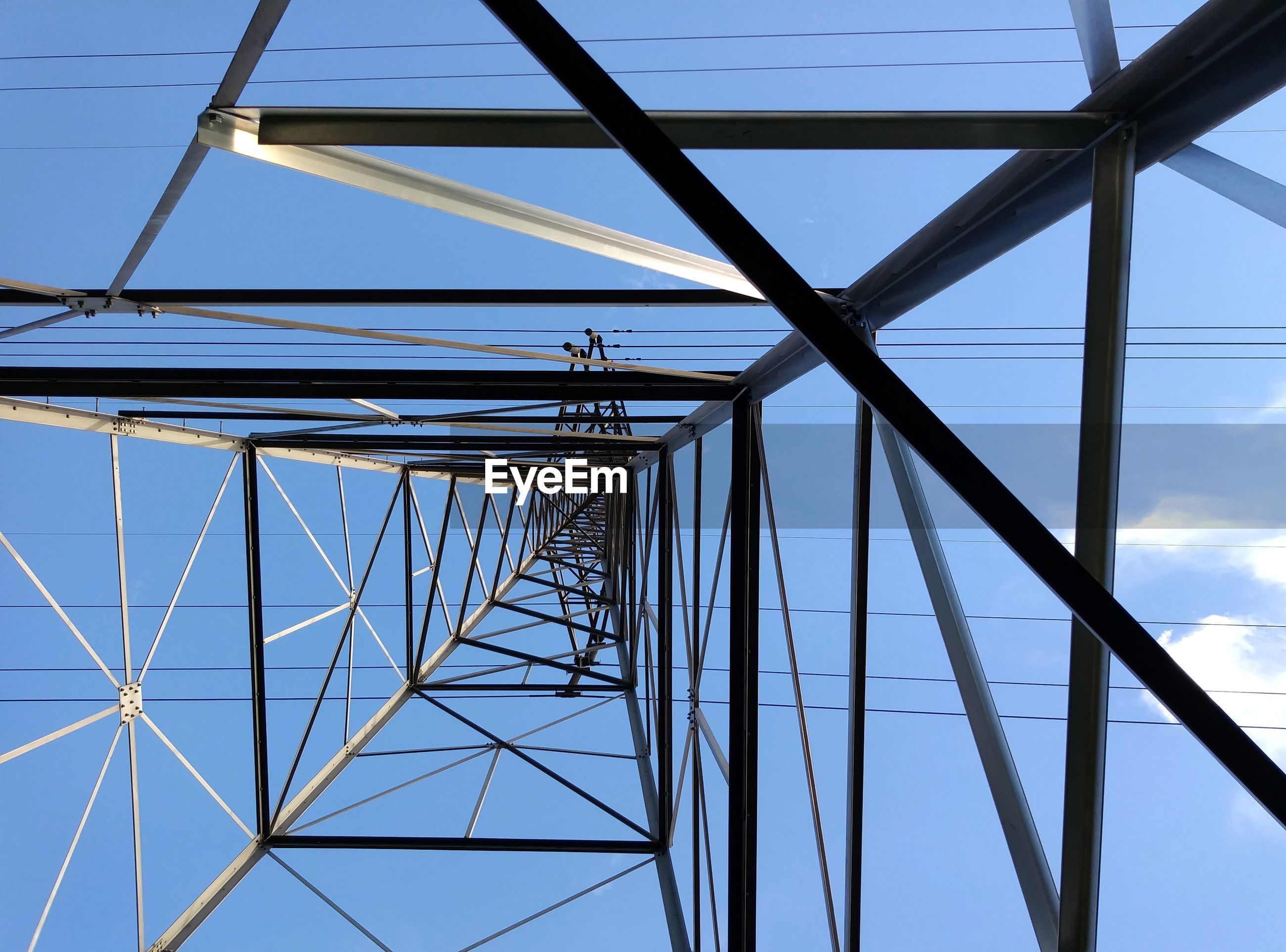 DIRECTLY BELOW SHOT OF ELECTRICITY PYLON AGAINST SKY