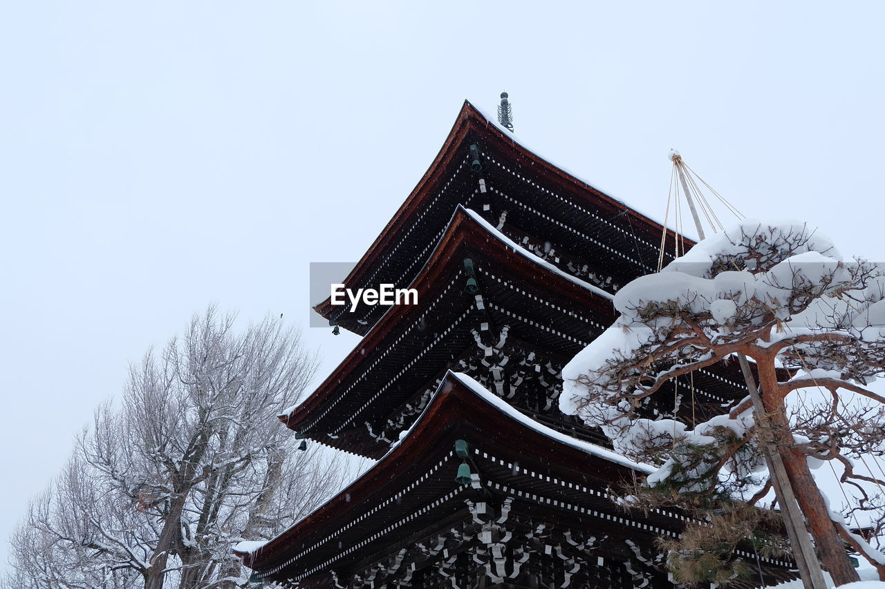 architecture, cold temperature, snow, built structure, winter, sky, building exterior, religion, belief, building, place of worship, low angle view, nature, no people, spirituality, roof, clear sky, tree, outdoors, eaves, snowing, snowcapped mountain