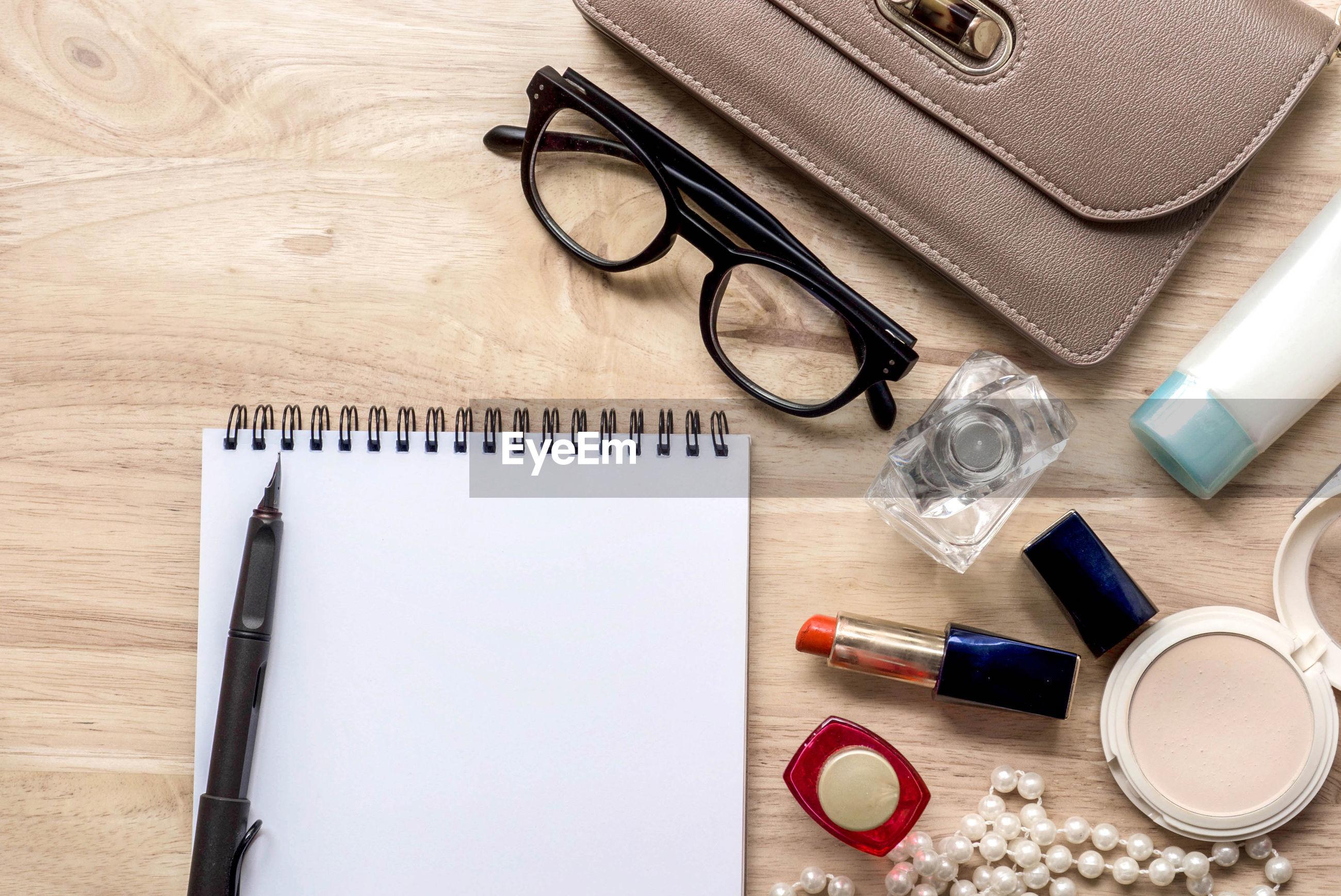High angle view of eyeglasses and make-up on table