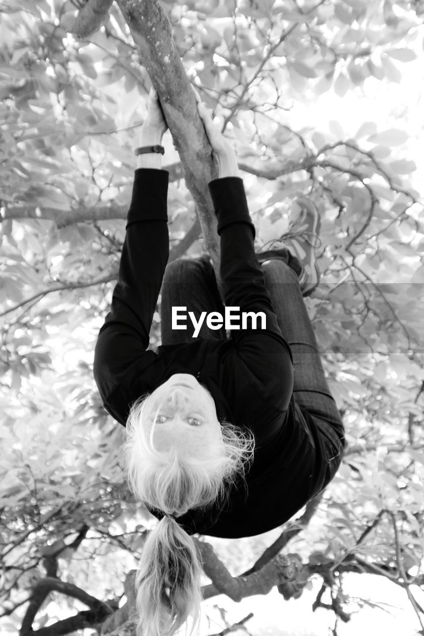 tree, plant, real people, nature, lifestyles, leisure activity, day, one person, branch, full length, women, upside down, exercising, healthy lifestyle, portrait, casual clothing, outdoors, flexibility, park