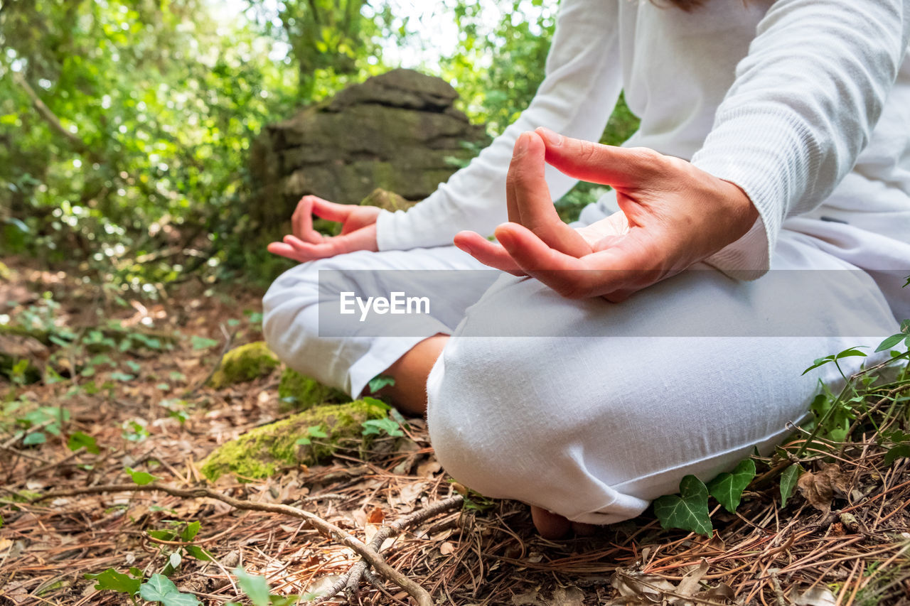 Midsection Of Woman Meditating In Forest