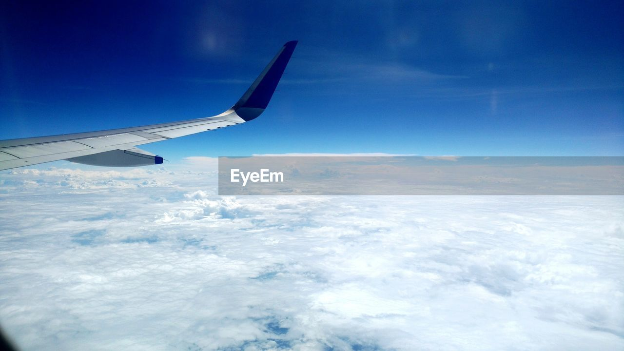 airplane, transportation, journey, sky, aerial view, airplane wing, nature, flying, cloud - sky, travel, beauty in nature, aircraft wing, no people, scenics, air vehicle, mode of transport, blue, tranquil scene, mid-air, outdoors, tranquility, day, landscape