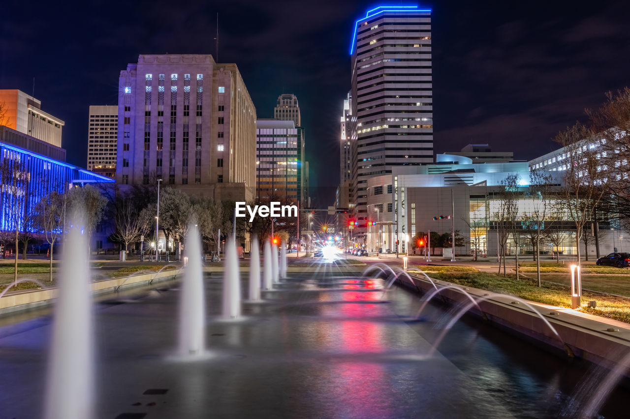 architecture, building exterior, built structure, illuminated, city, night, motion, building, water, blurred motion, long exposure, sky, nature, transportation, no people, city life, street, office building exterior, speed, cityscape, outdoors, skyscraper