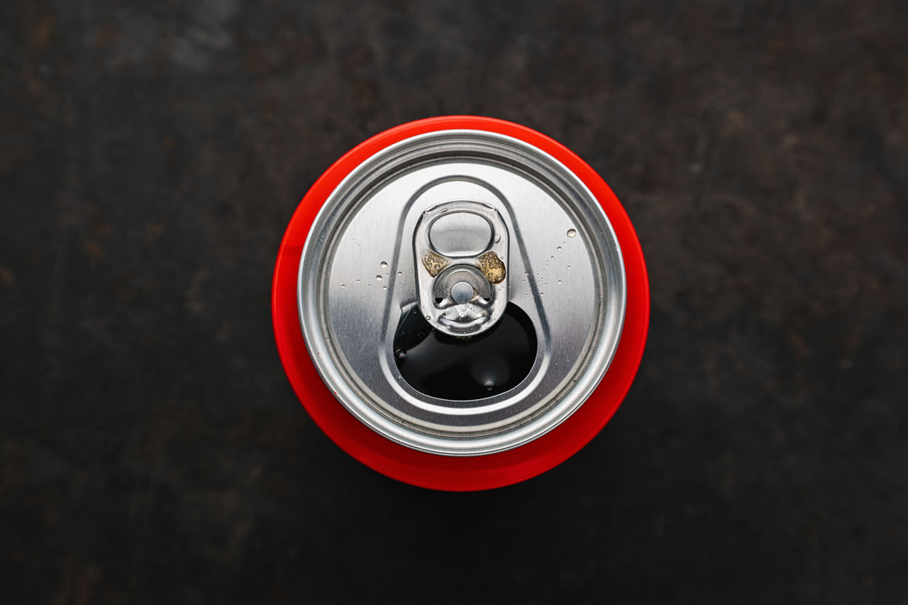 metal, close-up, directly above, no people, focus on foreground, red, silver colored, shape, high angle view, circle, geometric shape, food and drink, day, drink, indoors, can, still life, drink can, security