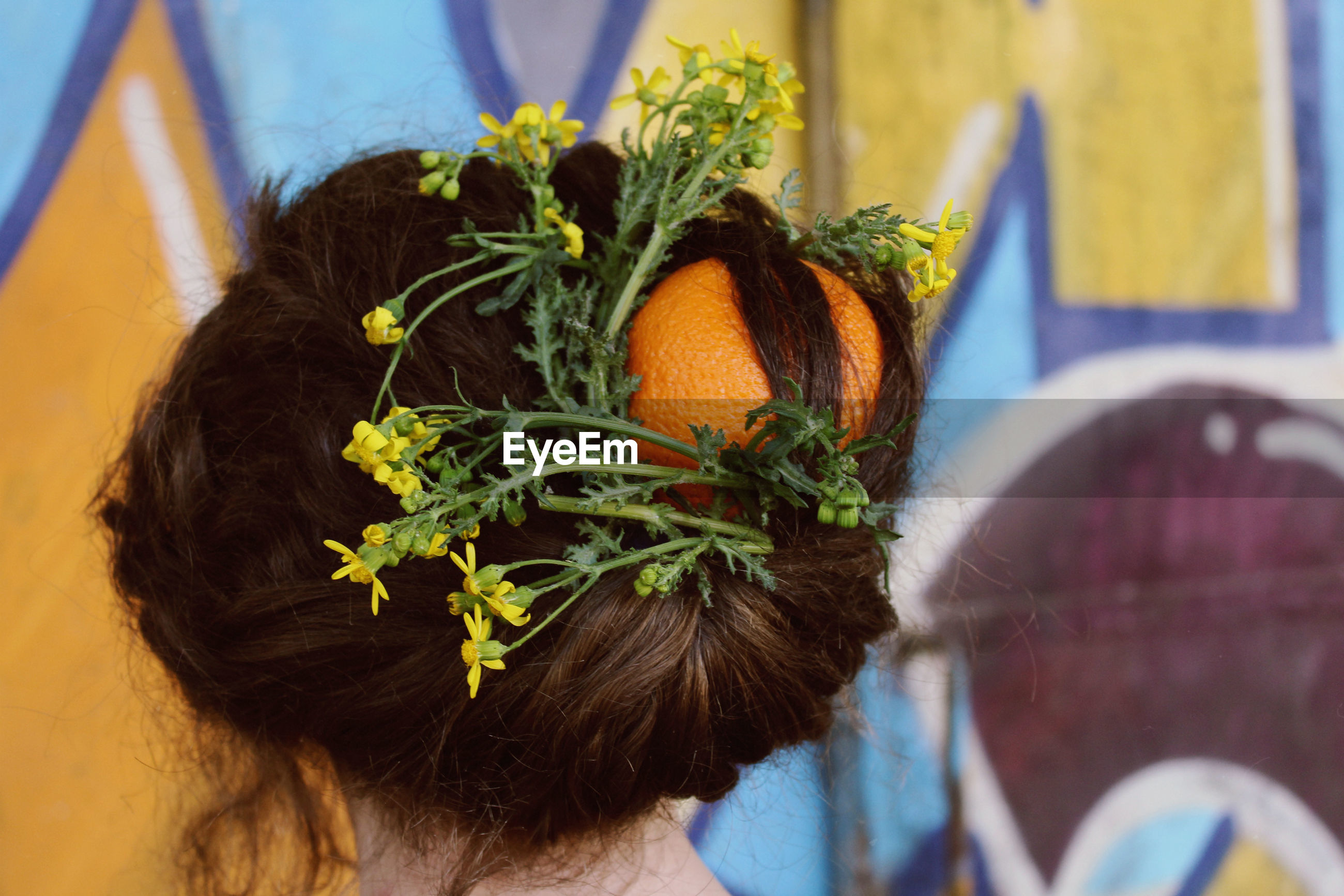 Rear view of woman with flowers and orange in hair