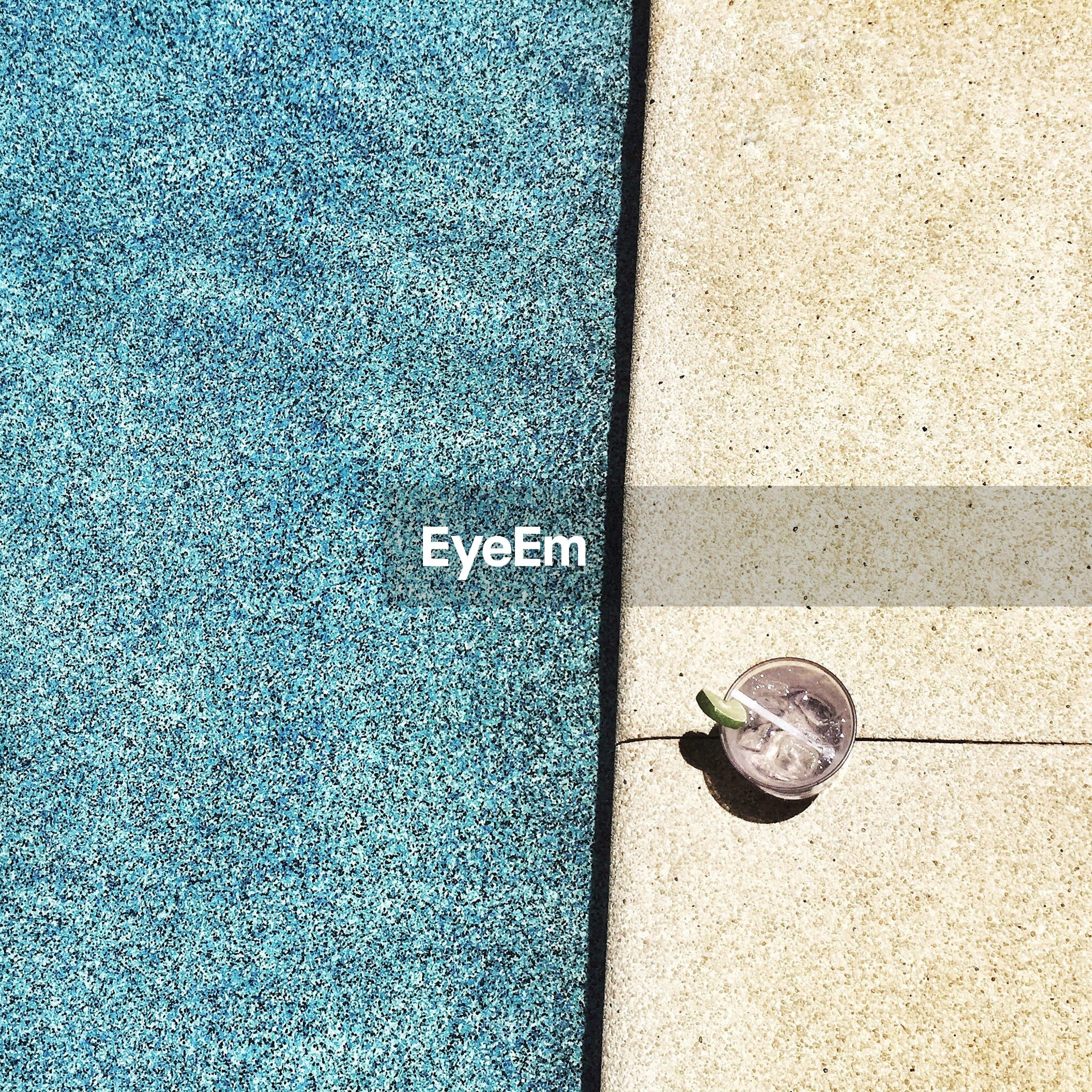 High angle view of drink at poolside during sunny day