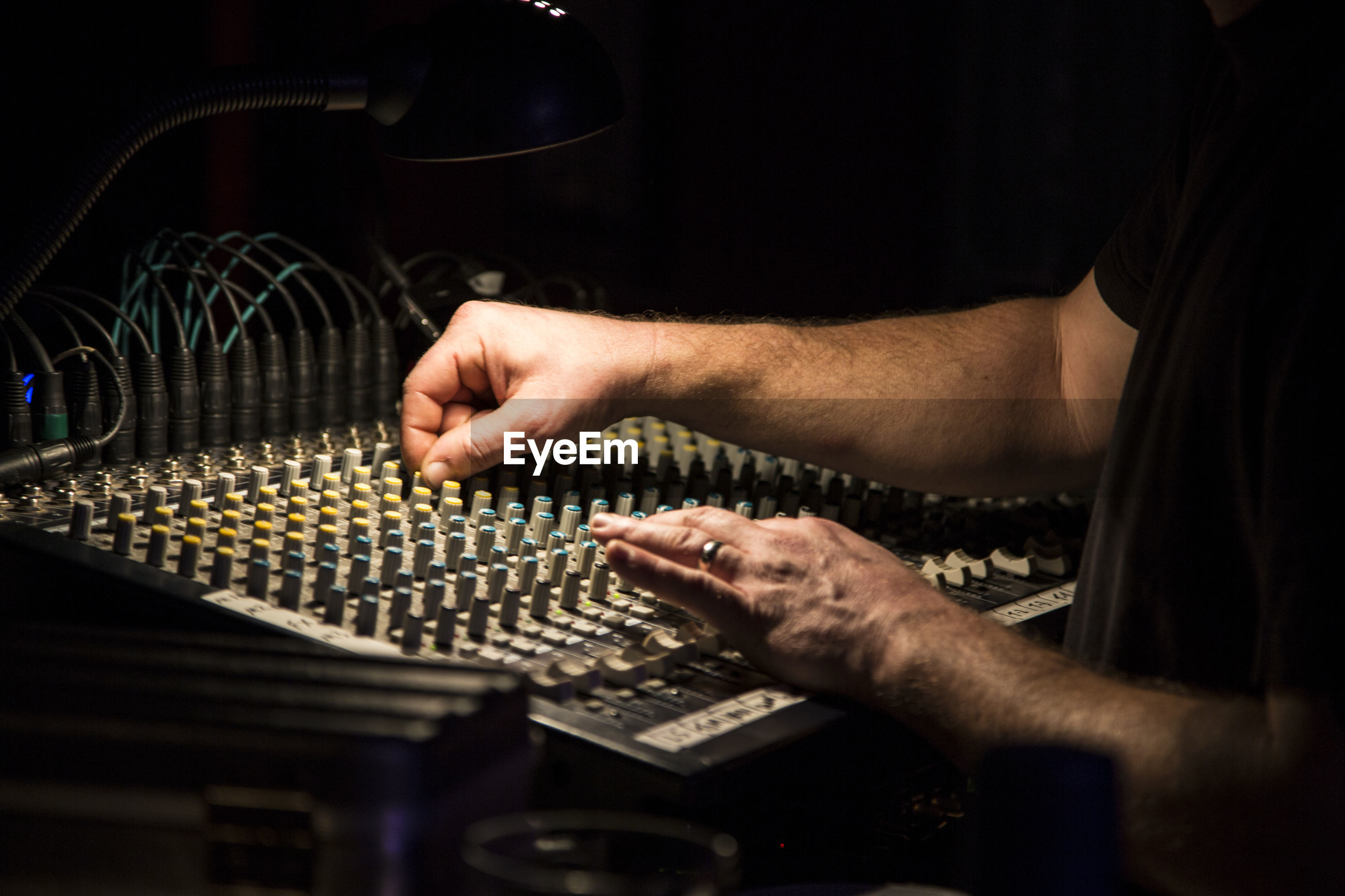 Midsection of man using sound mixer in recording studio