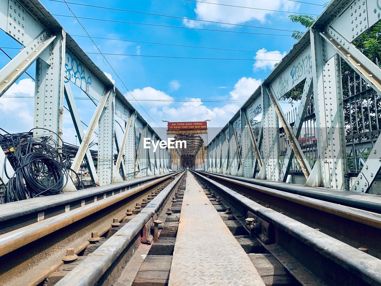 transportation, rail transportation, track, railroad track, connection, bridge, architecture, sky, built structure, diminishing perspective, bridge - man made structure, the way forward, direction, cloud - sky, mode of transportation, metal, nature, day, railway bridge, vanishing point, no people, outdoors, long