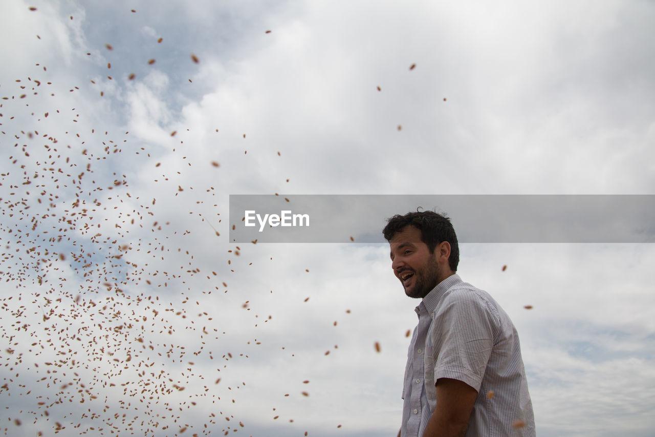 Smiling farmer standing against sky