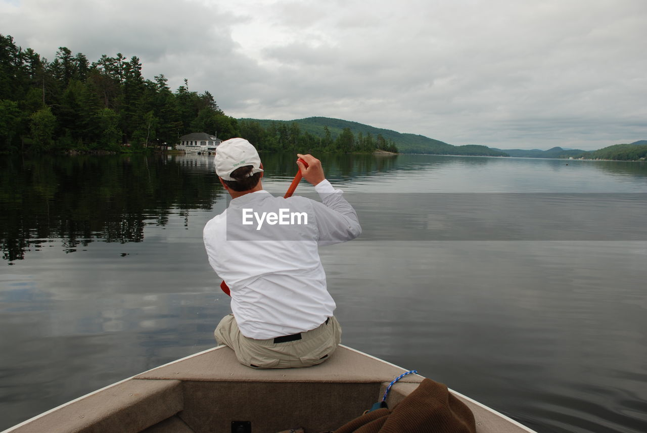 Rear view of man sitting on boat in river against sky
