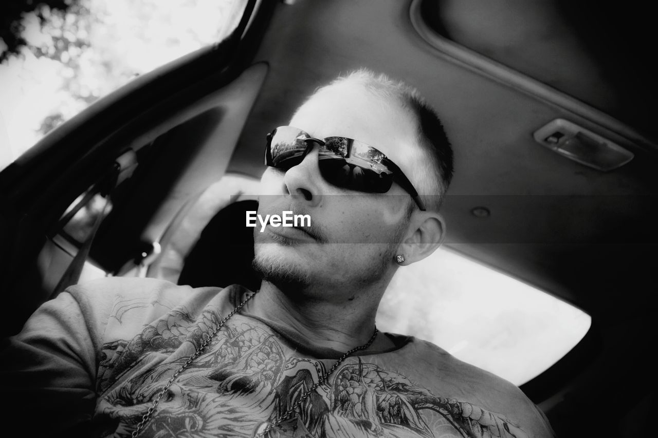 Man wearing sunglasses while sitting in car