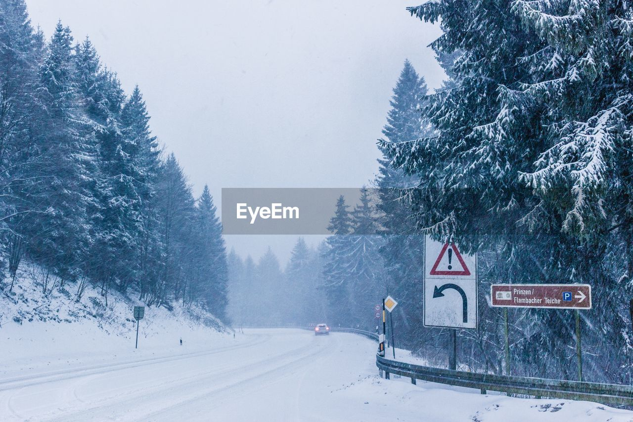 cold temperature, winter, snow, tree, plant, transportation, nature, beauty in nature, road, sign, covering, day, scenics - nature, mountain, land, mode of transportation, road sign, communication, no people, snowing, outdoors, extreme weather