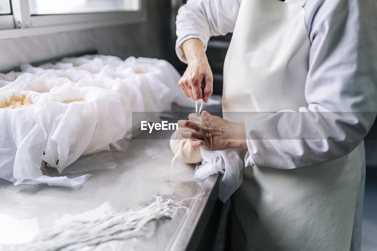 MIDSECTION OF MAN PREPARING FOOD AT KITCHEN