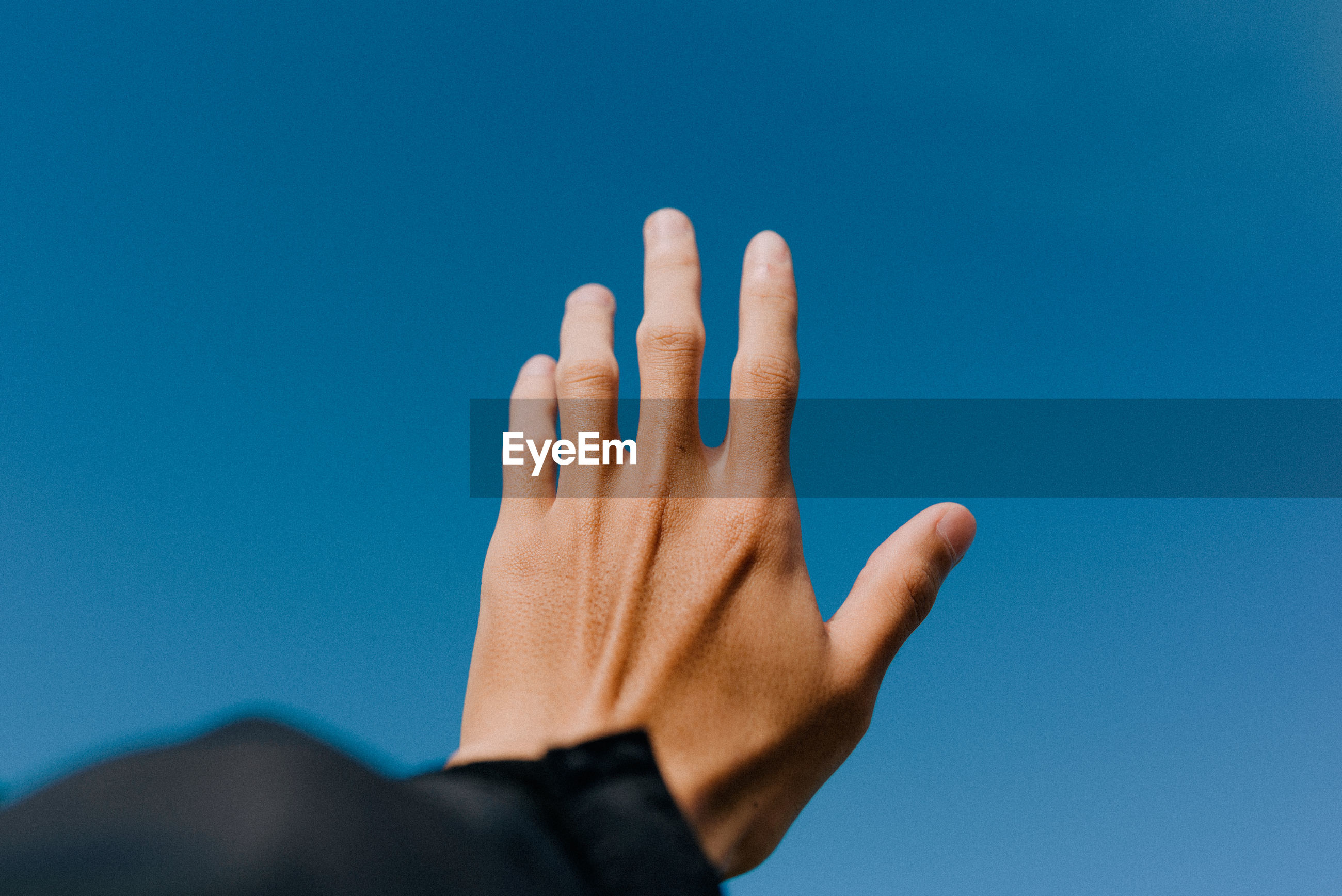 Cropped hand of man reaching towards clear blue sky