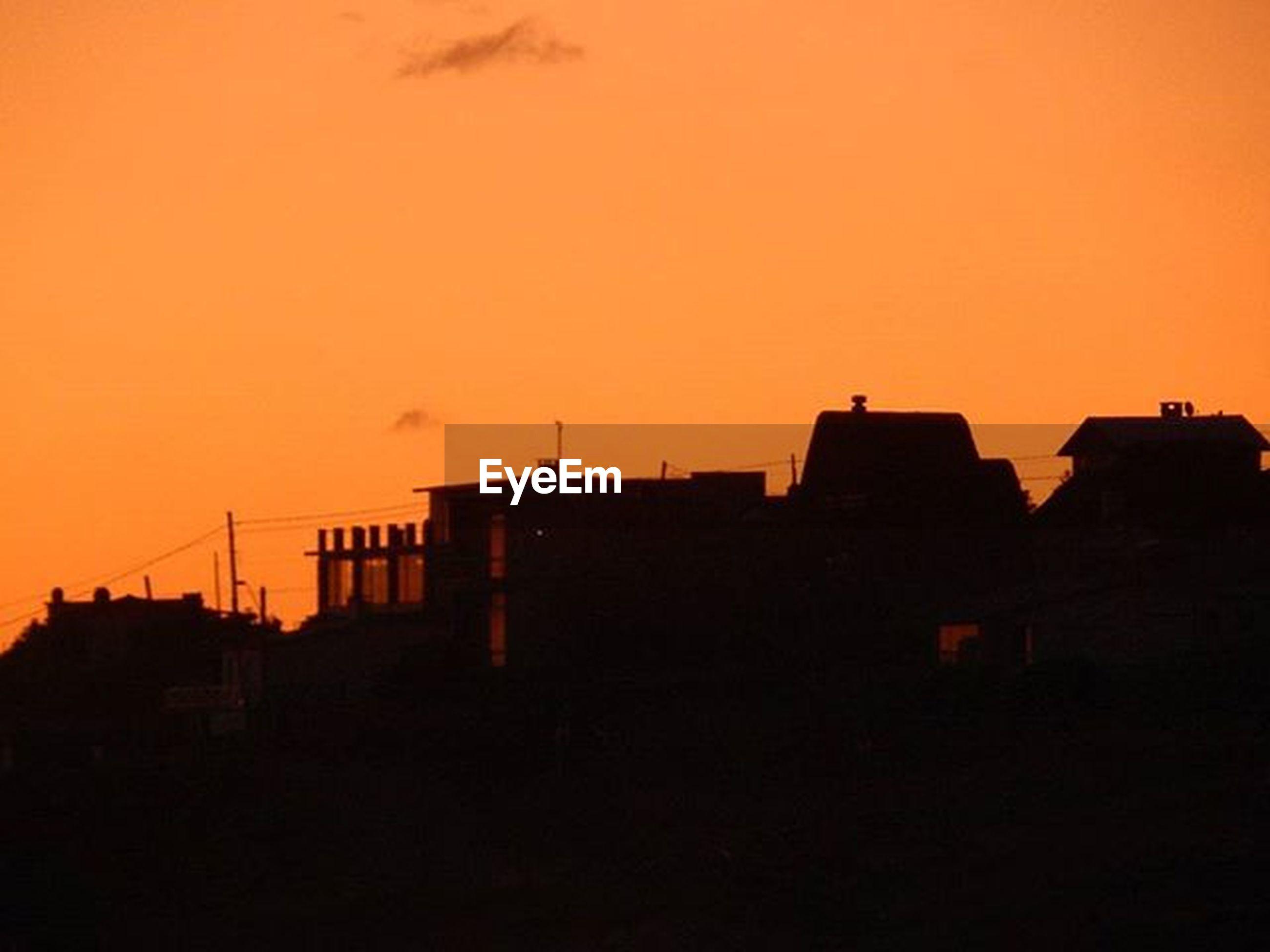 sunset, architecture, building exterior, built structure, silhouette, orange color, copy space, house, residential structure, residential building, clear sky, building, city, sky, outdoors, low angle view, dusk, no people, nature, development