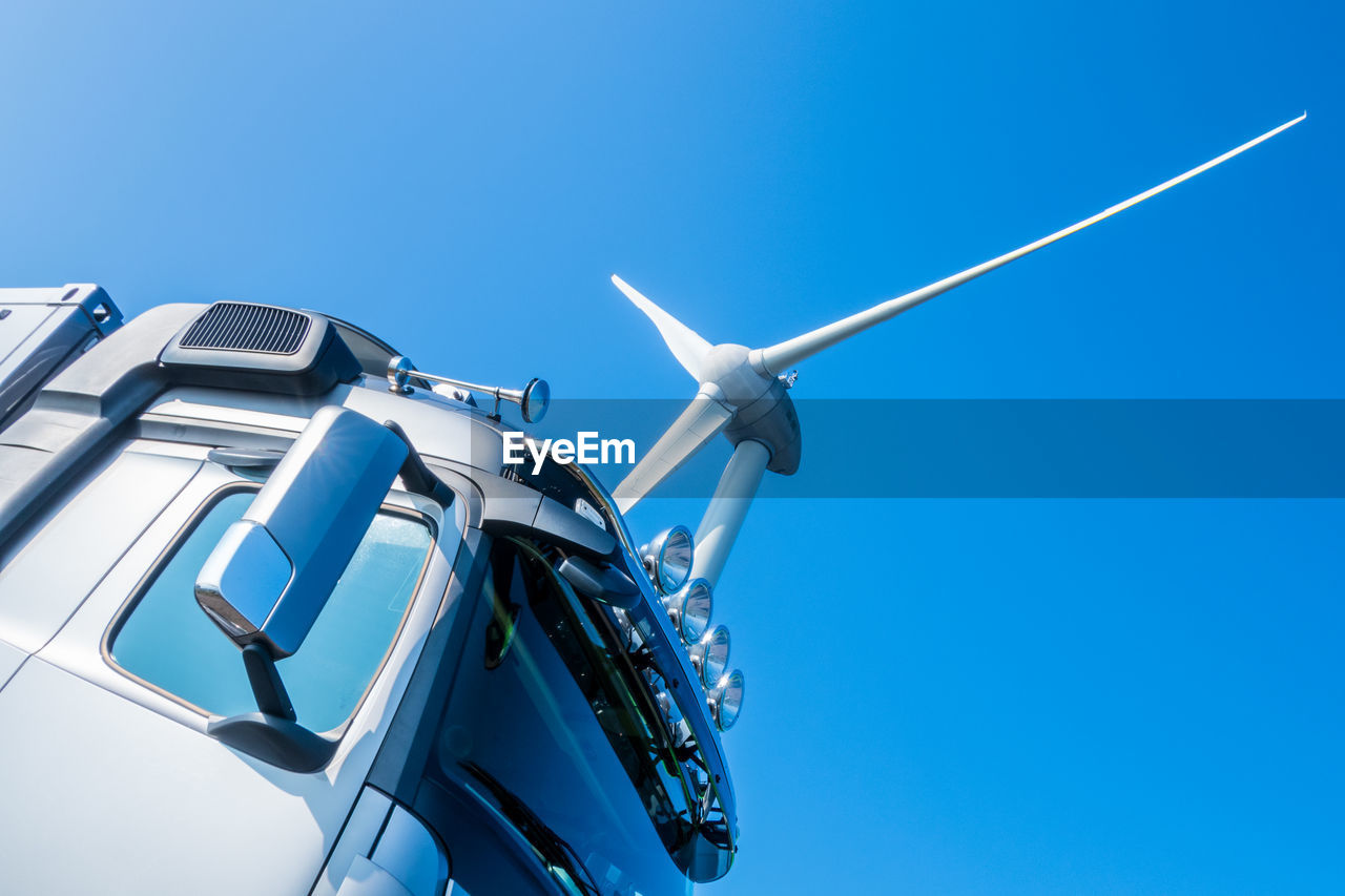 Low angle view of truck and wind turbine against clear blue sky