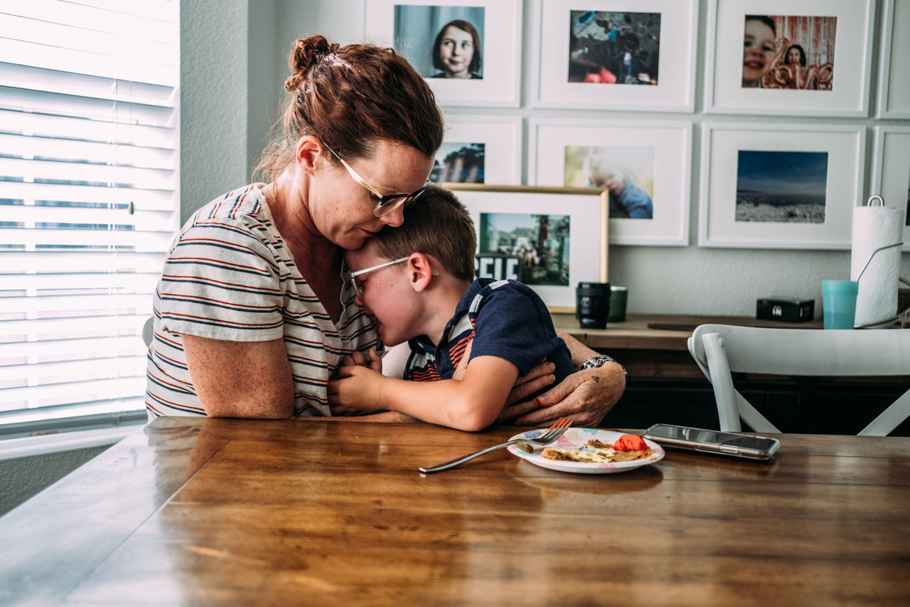 HAPPY MOTHER AND SON ON TABLE IN KITCHEN