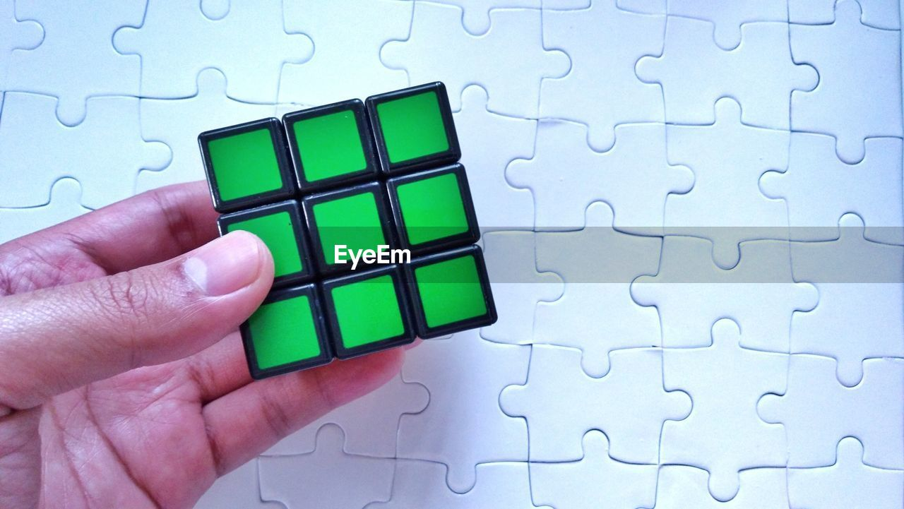 Cropped Hand Holding Block By Puzzle